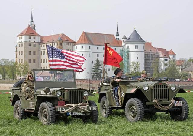 Amateur actors stand with their historical jeeps decorated with the US and the former Soviet Union flags in front of the Torgau Castle during the 70th anniversary celebrations of the so-called Elbe Day in Torgau, eastern Germany, Saturday, April 25, 2015. The WW II link-up of US and Soviet Forces occurred here at the river Elbe on April 25, 1945. (Photo by Jens Meyer/AP Photo)