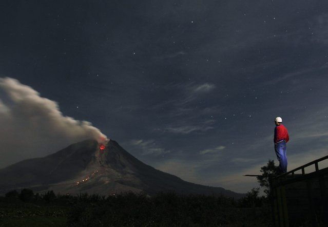 A man looks at Mount Sinabung spewing ash from Jraya village in Karo district, Indonesia's North Sumatra province, January 13, 2014. (Photo by Reuters/Roni Bintang)