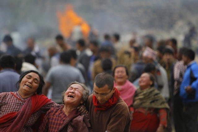 Family members break down during the cremation of earthquake victims in Bhaktapur near Kathmandu, Nepal, Sunday, April 26, 2015. (Photo by Niranjan Shrestha/AP Photo)
