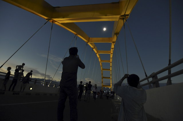 People watch a total solar eclipse from the Bay Bridge in Palu, Central Sulawesi, Indonesia March 9, 2016 in this photo taken by Antara Foto. (Photo by Mohamad Hamzah/Reuters/Antara Foto)