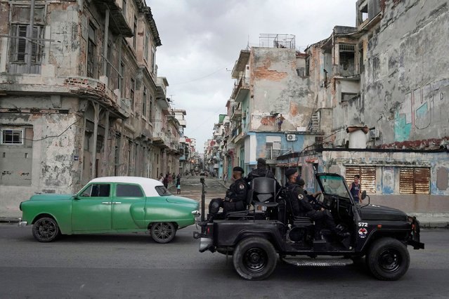 A special forces vehicle passes by a vintage car in downtown Havana, Cuba, July 13, 2021. (Photo by Alexandre Meneghini/Reuters)