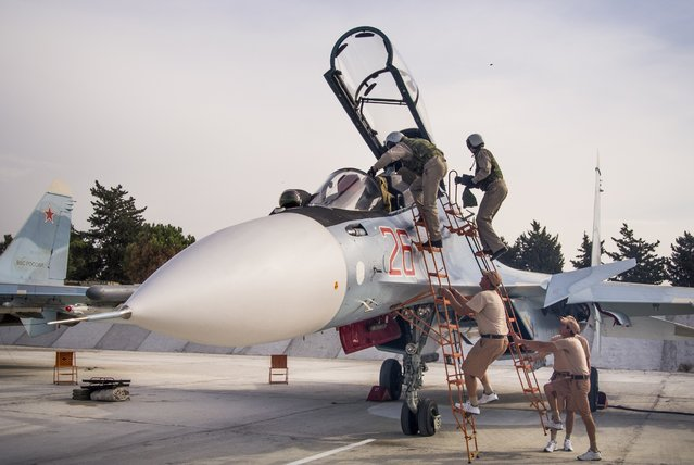 In this file photo taken on Thursday, October 22, 2015, Russian air force pilots assisted by ground crew climb into their fighter jet at Hemeimeem airbase, Syria. (Photo by Vladimir Isachenkov/AP Photo)