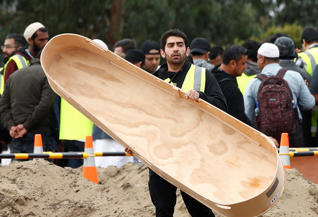 People attend the burial ceremony of a victim of the mosque attacks at the Memorial Park Cemetery in Christchurch, New Zealand March 21, 2019. (Photo by Edgar Su/Reuters)
