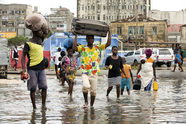 In this photo taken on Friday, March 15, 2019 and provided by the International Red Cross, people carry their personal effects after Tropical Cyclone Idai, in Beira, Mozambique. Mozambique's President Filipe Nyusi says that more than 1,000 may have by killed by Cyclone Idai, which many say is the worst in more than 20 years. Speaking to state Radio Mozambique, Nyusi said Monday, March 18 that although the official death count is currently 84, he believes the toll will be more than 1,000. (Photo by Denis Onyodi/IFRC via AP Photo)