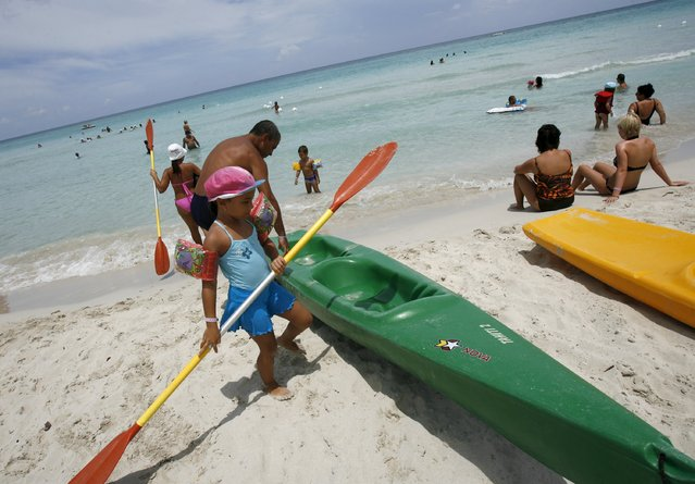 Vacationing Cubans get ready to board a kayak near a beachfront hotel in Varadero, 90 miles (145 km) east of Havana in this August 5, 2008 file picture. Americans traveling to Cuba later this month are being moved out of Havana hotels to make room for President Barack Obama's entourage and being sent tantalizingly close to a place U.S. law forbids them from visiting: the beach. (Photo by Claudia Daut/Reuters)