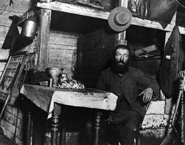 A Jewish cobbler ready for Sabbath Eve in a coal cellar in New York, where he is living with his family, 1887