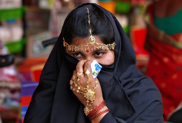 A bride covers her face as she waits to take her wedding vow during a mass marriage ceremony in which, according to its organizers, 109 tribal, Muslim and Hindu couples from various villages across the state took their wedding vows, at Bahirkhand village, north of Kolkata, India February 5, 2017. (Photo by Rupak De Chowdhuri/Reuters)