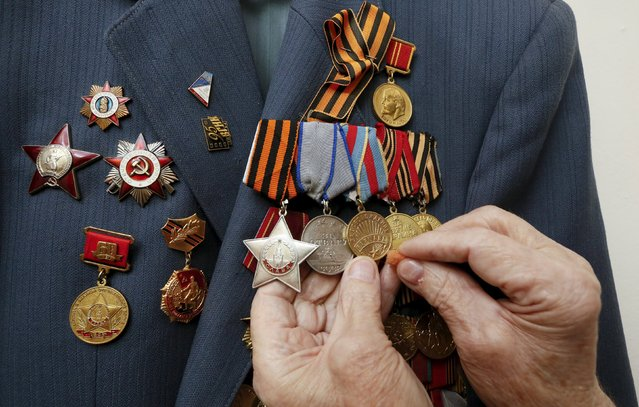 Alexei Samokhin, a 90-year-old World War Two veteran and companion of the Order of Glory, cleans his medals at his apartment as he prepares for the upcoming Victory Day, the 70th anniversary of the end of World War Two, in the Siberian town of Divnogorsk, Russia May 7, 2015. (Photo by Ilya Naymushin/Reuters)