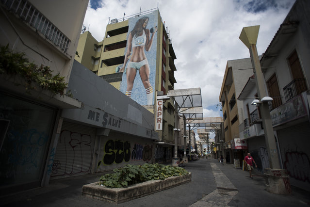 Shops are shuttered in the Paseo de Diego in San Juan, Puerto Rico, Wednesday, April 17, 2019. This central thoroughfare in Rio Piedras was filled years ago with stores that are closed and empty today. (Photo by Carlos Giusti/AP Photo)