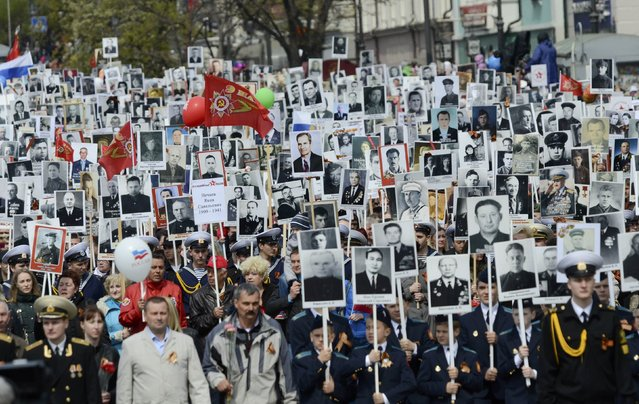 People hold pictures of World War Two soldiers as they take part in the Immortal Regiment march during the Victory Day parade in Vladivostok, Russia, May 9, 2015. (Photo by Yuri Maltsev/Reuters)
