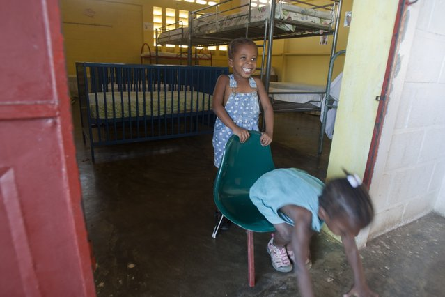 In this April 6, 2015 photo, Jean Michelle Gina Nancy holds the chair as she plays with her friend Pierre Catherina, both four-years-old, at the entrance of their room at the Mercy & Sharing residential center in the community of Williamson, Arcahaie, Haiti. Both girls were abandoned by their families at a government hospital before their first birthdays. (Photo by Dieu Nalio Chery/AP Photo)