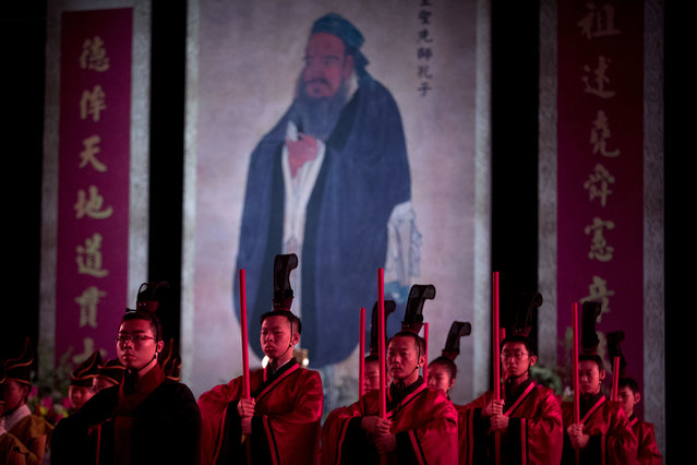 In this Sept. 28, 2016 file photo, participants in traditional dress stand near an oversized portrait of Confucius during a ceremony to observe the 2567th anniversary of his birth in Beijing. A Chinese government department announced on Monday, May 27, 2019, that China is running five-day Confucian culture immersion courses for religious leaders in the sage's hometown as part of a campaign to extend government control over faith communities through a process of sinicization. (Photo by Mark Schiefelbein/AP Photo/File)