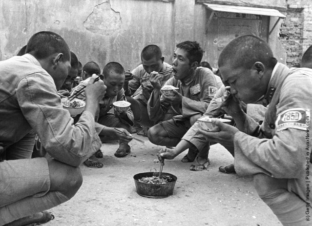 1939: A group of Chinese soldiers squatting and eating from bowls with chopsticks