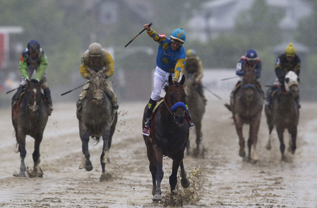 American Pharoah, ridden by Victor Espinoza, center, wins the 140th Preakness Stakes horse race at Pimlico Race Course, Saturday, May 16, 2015, in Baltimore. (Photo by Patrick Semansky/AP Photo)