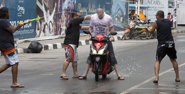 In this April 13, 2015 file photo,  tourist is showered in water by locals during the Songkran festival to celebrate the Thai New Year on Samui Island in Surat Thani province, Thailand. Thailand's military government is putting a dampener on the annual nationwide water fight. Despite Thailand's worst drought in 20 years, the junta says it has no intention of limiting the virtually around-the-clock water throwing that defines the three-day Songkran festival. Instead, it has decided to impose morality measures. (Photo by Mark Baker/AP Photo)