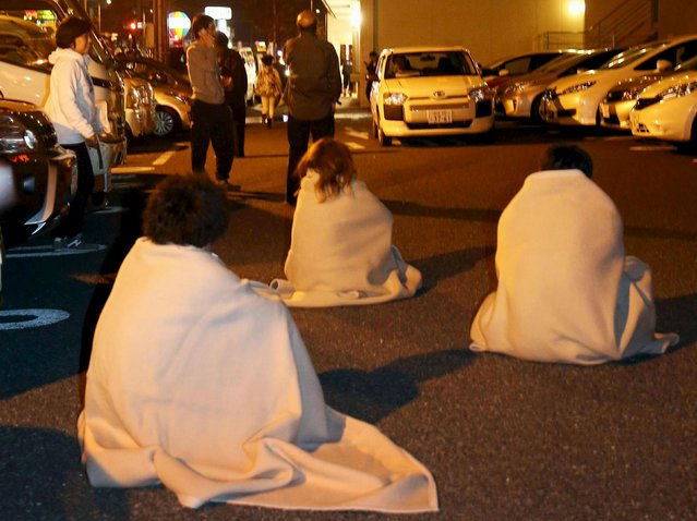 People wrapped in blankets sit on the road as they are evacuated from a hotel after an earthquake in Kumamoto, southern Japan, in this photo taken by Kyodo April 14, 2016. (Photo by Reuters/Kyodo News)