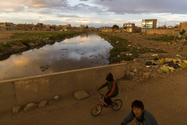 In this February 1, 2017 photo, children ride bikes along the Torococha River near a municipal waste treatment plant with water that flows into Lake Titicaca, in Juliaca, in the Puno region of Peru. Many of the more than 400,000 tourists who visit Lake Titicaca from Peru each year stop first in Juliaca, a town that produces 200 tons of trash daily, much of it winding up in a river that has turned into a conveyor belt of waste heading into the lake. (Photo by Rodrigo Abd/AP Photo)
