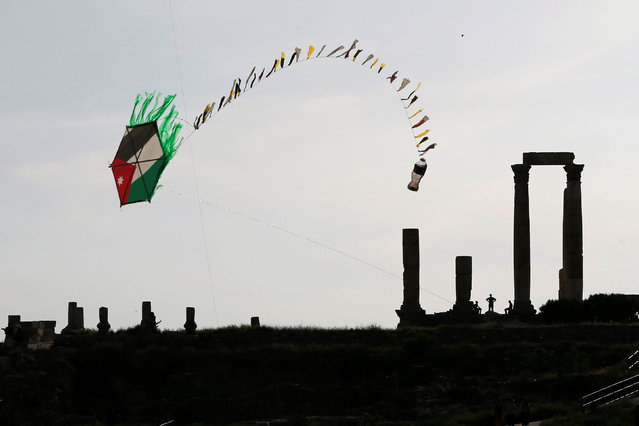 A kite decorated with the Jordanian national flag flies next the pillars of the Roman Temple of Hercules during an event celebrating spring at the Citadel in Amman, Jordan, April 15, 2016. (Photo by Muhammad Hamed/Reuters)