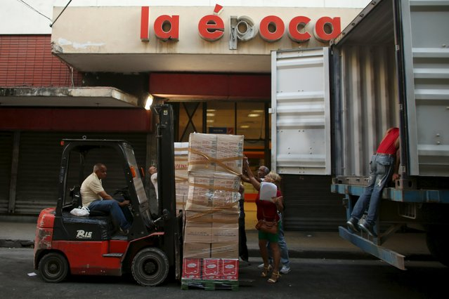 Workers unload products from a truck to a state-run shop in downtown Havana, April 12, 2016. (Photo by Alexandre Meneghini/Reuters)