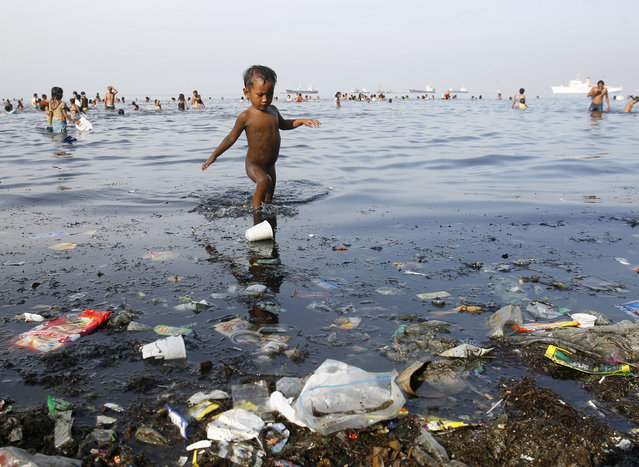 A boy paddles among garbage in the waters of Manila bay during Easter Sunday in Manila, Philippines on April 24, 2011. (Photo by Cheryl Ravelo/Reuters)