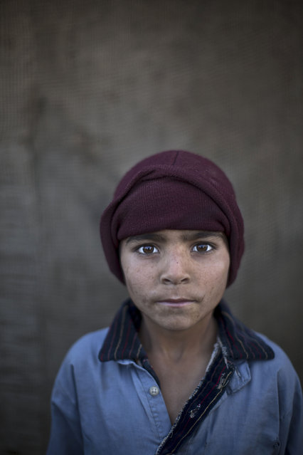 In this Sunday, January 26, 2014 photo, Afghan refugee boy, Noorkhan Zahir, 6, poses for a picture, while playing with other children in a slum on the outskirts of Islamabad, Pakistan. (Photo by Muhammed Muheisen/AP Photo)