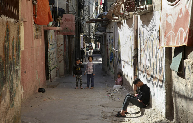 In this April 21, 2019 photo, a Palestinian teenager sits in an alley as children play in front of their family house, in the Shati refugee camp, in Gaza City. The blockade Israel and Egypt imposed on Gaza after the Hamas militant group took power in 2007 has ravaged the economy. The skyrocketing unemployment rates, combined with foreign aid cuts and Hamas' mismanagement, has left thousands of families dependent on food aid and social welfare. Many young Gazans have been forced to put off their dreams of marriage because they cannot afford it. (Photo by Adel Hana/AP Photo)