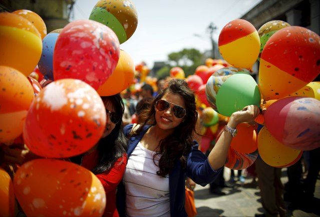 A woman holding balloons poses for a picture before releasing them during an event organized to commemorate the victims of last year's earthquakes in Kathmandu, Nepal, April 23, 2016. (Photo by Navesh Chitrakar/Reuters)