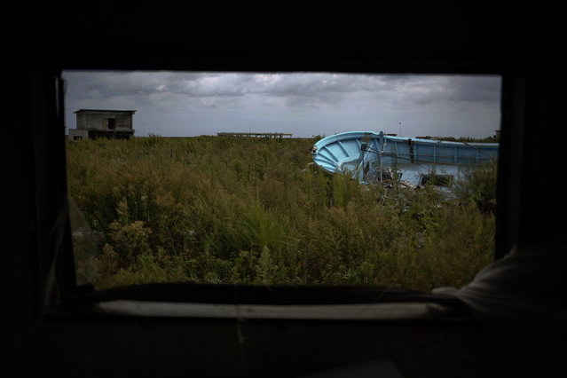 A fishing boat is seen on a field from inside an abandoned house in the evacuated town of Namie, September 23, 2013. (Photo by Damir Sagolj/Reuters)