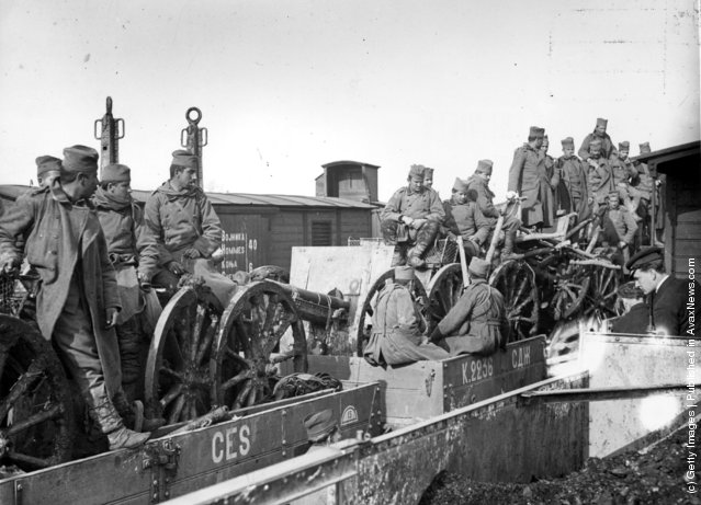 1915:  Serbian soldiers and artillery in railway trucks bound for the frontier