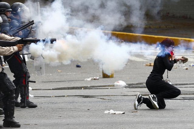Venezuela's national police fire tear gas as an anti-government protester kneels holding a rock during riots in Caracas April 6, 2014. Protesters have been on the streets since early February calling for President Nicolas Maduro's resignation and complaining about a litany of problems from rampant crime to food shortages.The government says they are seeking a coup against Maduro. (Photo by Carlos Garcia Rawlins/Reuters)