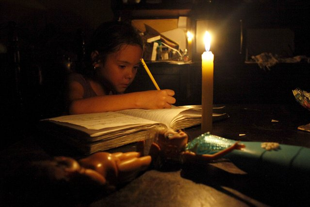 A girl does her homework by candlelight at his home during a power cut in San Cristobal, in the state of Tachira, Venezuela, April 25, 2016. (Photo by Carlos Eduardo Ramirez/Reuters)
