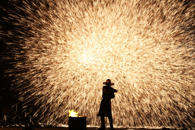 A folk artist performs molten iron fireworks at Hengnan County on July 17, 2019 in Hengyang, Hunan Province of China. (Photo by VCG/VCG via Getty Images)