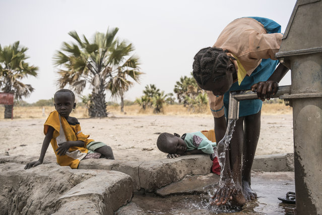 In this photo taken Sunday, March 12, 2017, a girl Abuk washes her legs at a water point four kilometers from her home in Aweil, in South Sudan. (Photo by Mackenzie Knowles-Coursin/UNICEF via AP Photo)