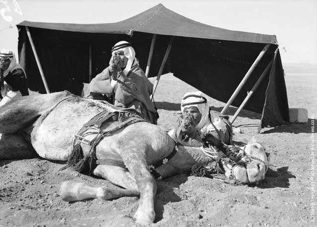 1936: Using their horse for cover, members of the Arab Legion stage a realistic 'Bedouin attack' at Amman, the capital of Jordan