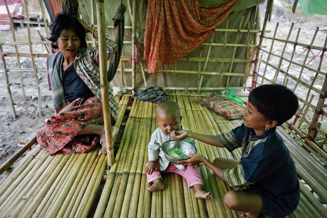 A baby is fed plain rice at a family tent at an oil field in the Minhla township of the Magwe district October 27, 2013. (Photo by Damir Sagolj/Reuters)