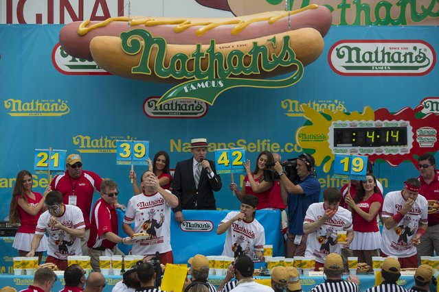Competitors consume hot dogs during the annual Fourth of July 2015 Nathan's Famous Hot Dog Eating Contest in Brooklyn, New York July 4, 2015. (Photo by Andrew Kelly/Reuters)