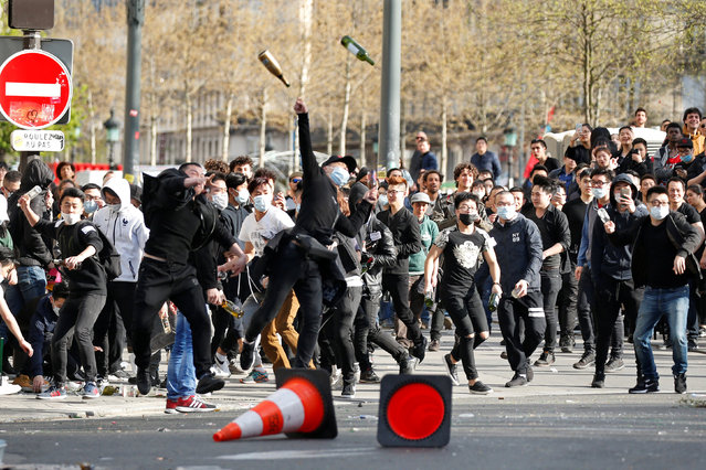 Prostesters throw bottles to French CRS riot police after a ceremony in memory of 56-year-old Shaoyao Liu, who was shot dead by police at his Paris home last Sunday, in Paris, France April 2, 2017. (Photo by Charles Platiau/Reuters)