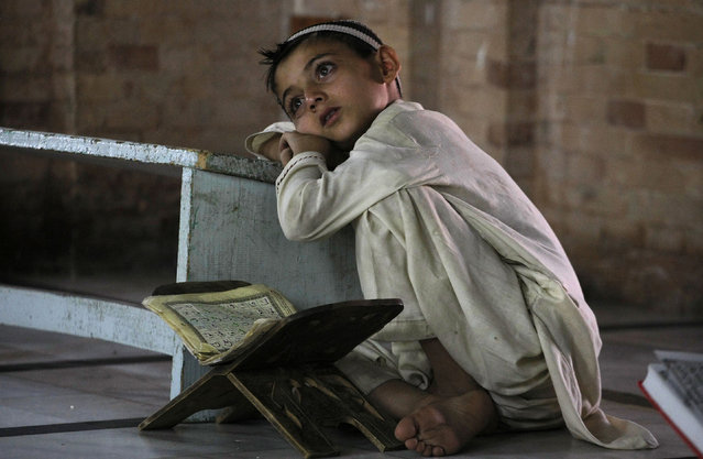 A Pakistani child takes a break during a class to learn the Quran at a mosque in Peshawar, Pakistan, Friday, July 3, 2015. Muslims across the world are observing the holy fasting month of Ramadan, where they refrain from eating, drinking and smoking from dawn to dusk. (Photo by Mohammad Sajjad/AP Photo)