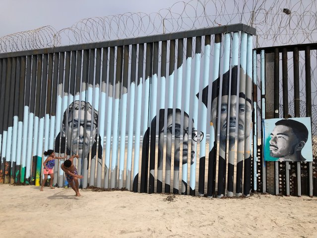 Children play in front of a new mural on the Mexican side of a border wall in Tijuana, Mexico Friday, August 9, 2019. The mural shows faces of people deported from the U.S. with barcodes that activate first-person narratives on visitors' phones. Lizbeth De La Cruz Santana conceived the interactive mural in Tijuana as part of doctoral dissertation at the University of California, Davis. (Photo by Elliot Spagat/AP Photo)