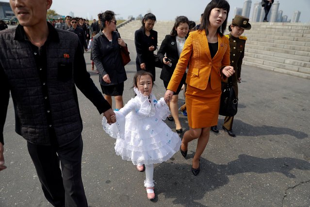 People arrive at the flower exhibition marking the 105th birth anniversary of the country's founding father, Kim Il Sung in Pyongyang, North Korea April 16, 2017. (Photo by Damir Sagolj/Reuters)