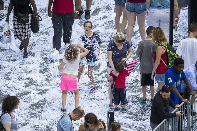 Fans of the U.S. women's soccer team play with confetti after a ticker tape parade to celebrate their World Cup final win over Japan on Sunday, in New York, July 10, 2015. (Photo by Lucas Jackson/Reuters)