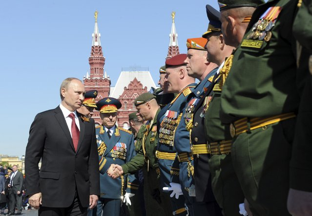 Russian President Vladimir Putin (L) meets servicemen during celebrations to mark Victory Day in Moscow's Red Square May 9, 2014. Putin praised the Soviet role in defeating fascism on Friday, the anniversary of the World War Two victory over Nazi Germany, and said those who defeated fascism must never be betrayed. (Photo by Mikhail Klimentyev/Reuters)