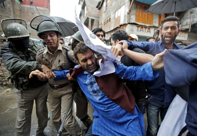Indian police officers try to detain Javid Mir (C), a leader of the moderate faction of the All Parties Hurriyat (Freedom) Conference (APHC), during a march in Srinagar July 13, 2015. Indian police on Monday stopped the supporters of APHC when they tried to march towards the Martyrs graveyard in Srinagar to mark Martyrs Day. (Photo by Danish Ismail/Reuters)