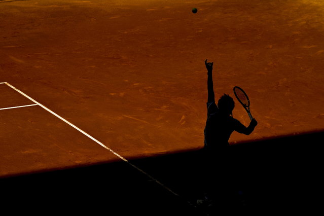Japanese tennis player Kei Nishikori's shadow is silhouetted on the court as he serves the ball against Croatian Ivan Dodig during their men's singles first round tennis match of the Mutua Madrid Open played at Caja Magica complex in Madrid, Spain, on May 5, 2014. (Photo by Emilio Naranjo/EPA)