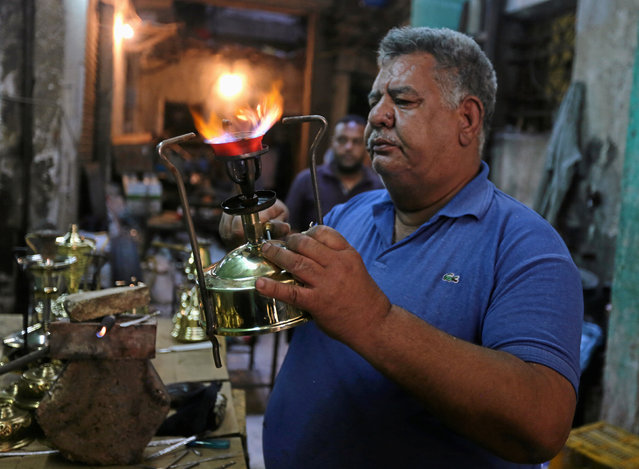"Mohamed Gamal Abdel Nasser, a workshop owner, tests primus stoves known as ""Bagour"" in Arabic, in Cairo, Egypt, May 11, 2016. (Photo by Mohamed Abd El Ghany/Reuters)"