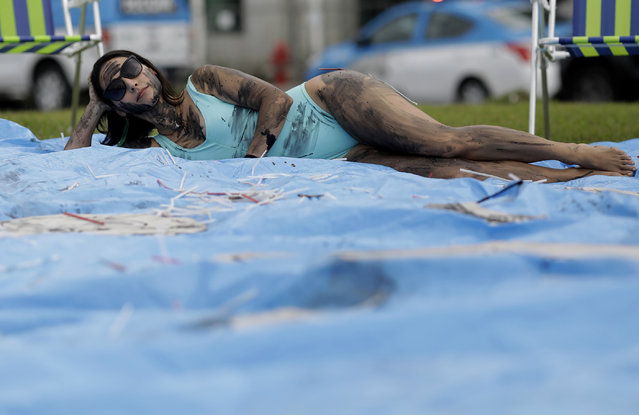 A demonstrator painted with fake oil lies on a tarp during a protest against the auction for the exploration of oil fields close to Abrolhos, a marine national park in Bahia state, in front of the Grand Hyatt Hotel where the auction is taking place, in Rio de Janeiro, Brazil, Thursday, October 10, 2019. Under pressure from environmental organizations, none of the 17 companies involved in the process presented any offers. (Photo by Silvia Izquierdo/AP Photo)