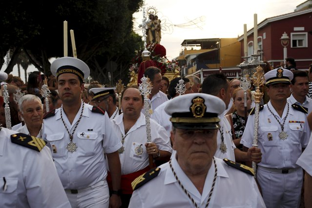 Sailors take part in the procession of the El Carmen Virgin (rear), on its way to be carried into the sea, in Malaga, July 16, 2015. Many seaside towns celebrate the annual feast of the El Carmen Virgin, who is worshipped as the patron saint of sailors. (Photo by Jon Nazca/Reuters)