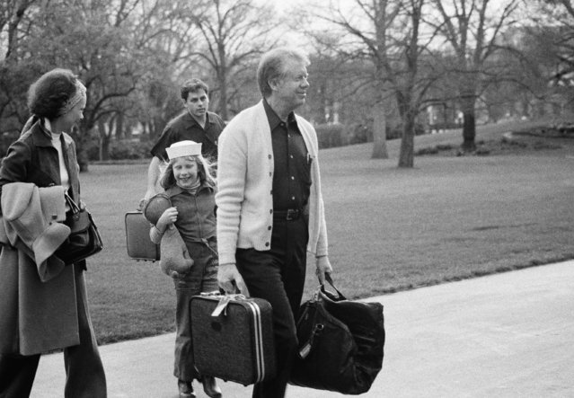 Pres. Jimmy Carter, right is followed by his daughter, Amy Carter, center, as they return to the White House after a weekend at Camp David, Sunday, March 28, 1977, Washington, D.C. It was their second weekend at Presidential retreat. First Lady Rosalynn Carter is at left. (Photo by Charles W. Harrity/AP Photo)