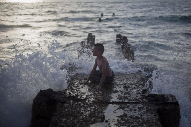 A Muslim boy sits on an old wave breaker at the Mediterranean Sea during the last day of the Eid al-Fitr holiday as the sun sets in Tel Aviv, Israel, Sunday, July 19, 2015. (Photo by Ariel Schalit/AP Photo)