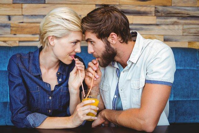 Cute couple on a date sharing a glass of orange juice. (Photo by Wavebreak Media ltd/Alamy Stock Photo)